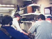 The nose cone being machined, while film crew look on